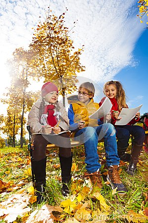 Three kids drawing and sitting on bench in autumn park
