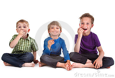 Three kids eating sweets
