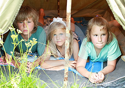 Three kids in an old tent