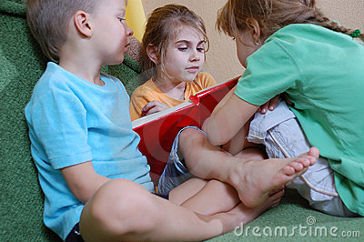 Three kids reading at home