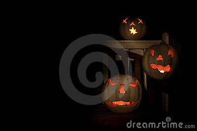 Three lit white jack o-lanterns on a bench