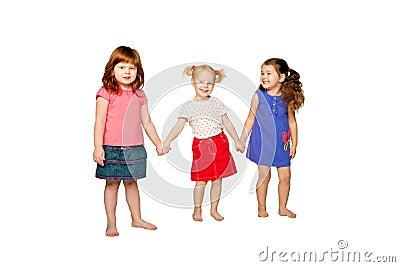 Three little girls holding hands.