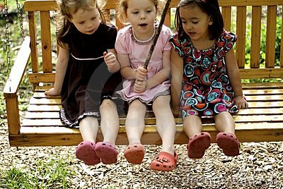 Three little girls on swing