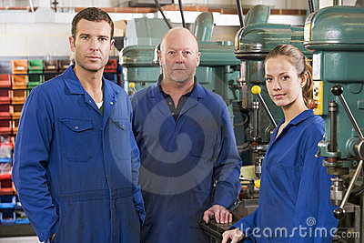 Three machinists in workspace by machine