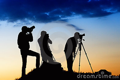 Three man silhouettes photographing the sky