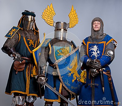 Three medieval knights in full armor standing