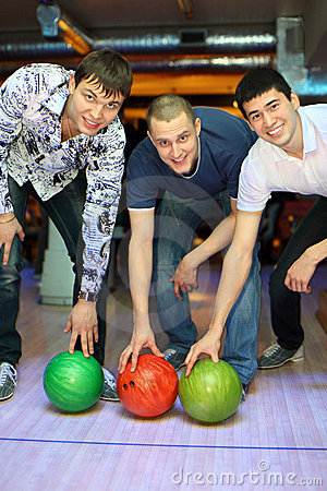 Three men bent over to heave up balls for bowling