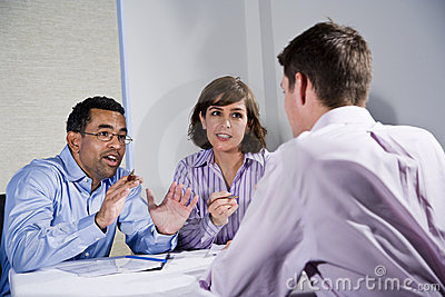 Three mid-adult people sitting at table meeting