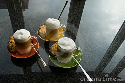 Three mugs with coffee and cream on dresser