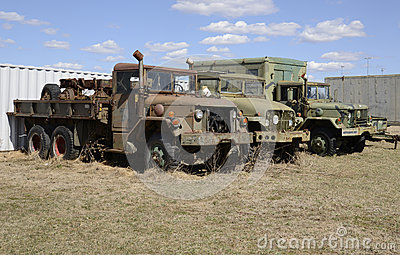 Three old army vehicles parked in a grass field