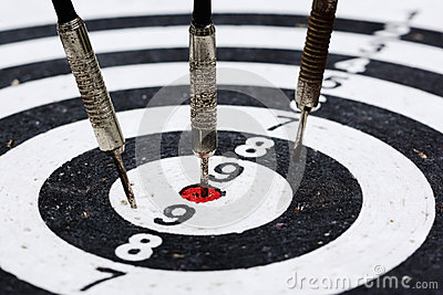 Three old darts hitting the target
