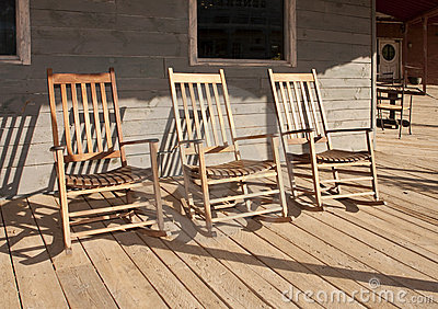 Three old West town empty rocking chairs