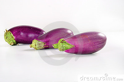 Three organic eggplant on white