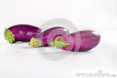 Three organic eggplant on white