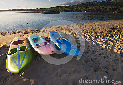 Three paddle boats or paddle skis on the beach