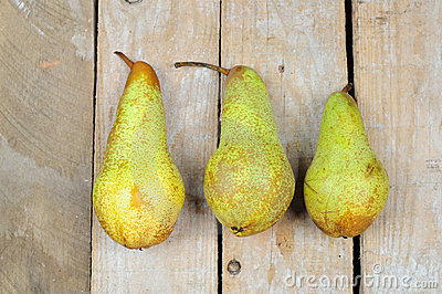 Three pears on wooden background