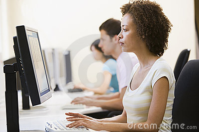 Three people in computer room typing