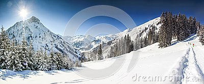 Three people hiking in mountains winter landscape with deep snow on clear sunny day. Allgau, Bavaria, Germany. Stock Photo