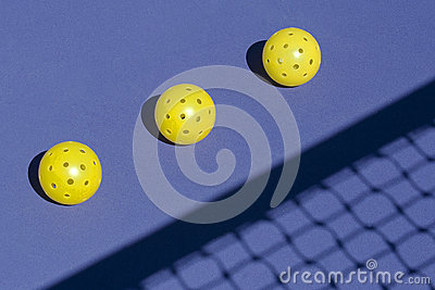 Three Pickleballs on Court with Net Shadow