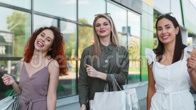 Three pretty shopper girl smiling dancing walking outdoor at window glass background. Medium shot. Attractive smiling woman friend enjoying shopping feeling stock video footage