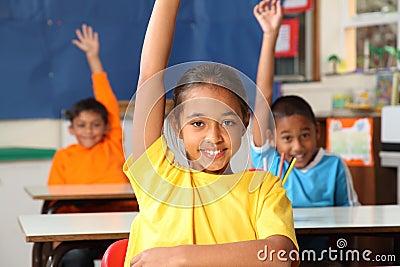 Three primary school children hands raised in clas