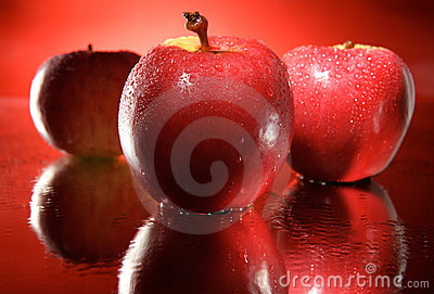 Three red apples background droplets