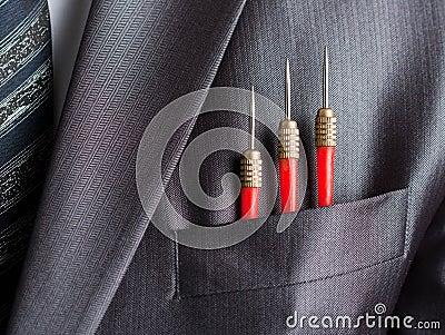Three red darts in businessman suit pocket
