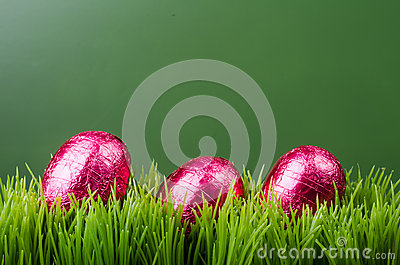 Three red foil Easter eggs on grass