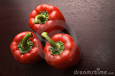 Three red peppers on dark wood