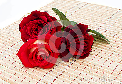 Three red roses are on a bamboo napkin
