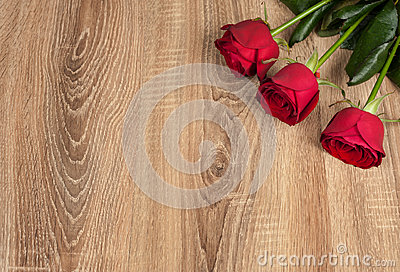 Three red roses on wood