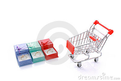 Three rings in gift boxes with empty shopping cart