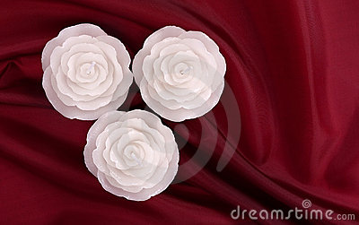 Three rose shaped candles on deep red satin
