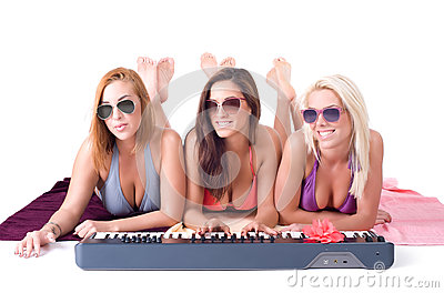 Three sexy girl lying on a towel and playing the synthesizer