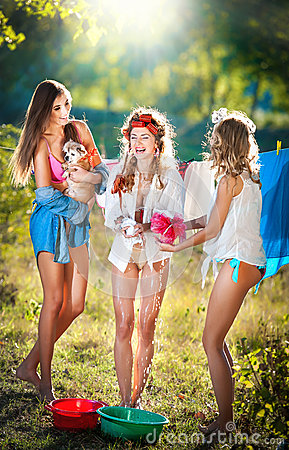 Free Three Sexy Women With Provocative Outfits Putting Clothes To Dry In Sun. Sensual Young Females Laughing Putting Out The Washing Stock Photos - 43333183