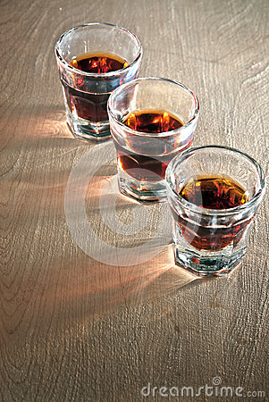 Three shot glasses full of dark colored alcohol