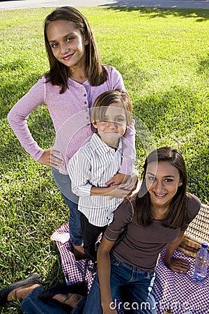 Three siblings having picnic in park