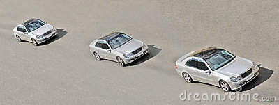 Three similar identical twins cars drive in a line