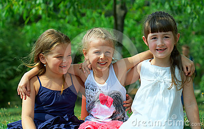 Three small girls embracing in summer park