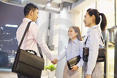 Three smiling business people handshaking outside the office at night