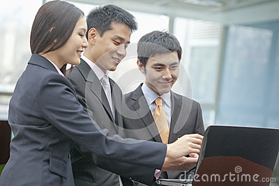 Three smiling business people looking at laptop and pointing, indoors