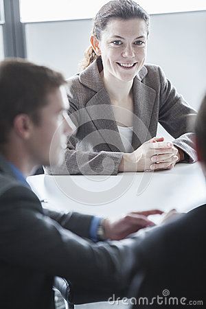 Three smiling business people sitting at a table and having a business meeting in the office