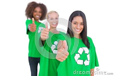 Three smiling enviromental activists giving thumbs up