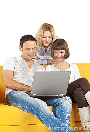 Three smiling friends with laptop computer