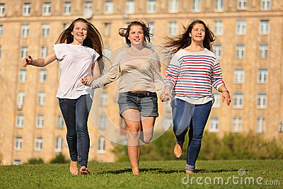 Three smiling girls run at grass and hold hands