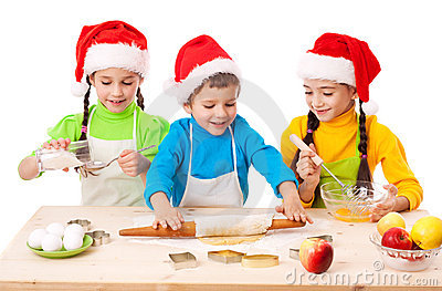 Three smiling kids with Christmas cooking