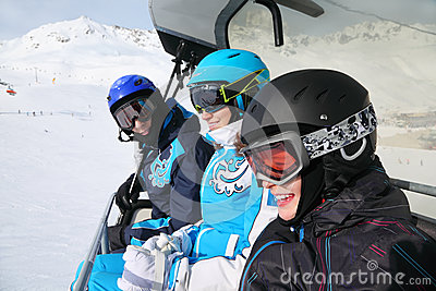 Three smiling skiers ride on funicular