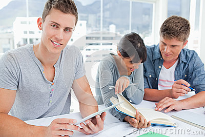 Three smiling students sitting and doing work