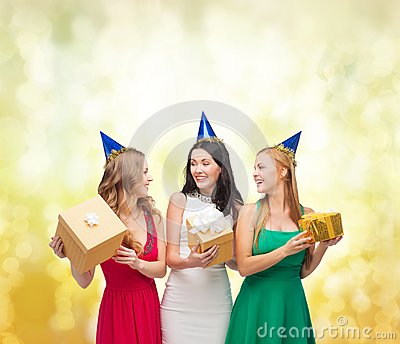 Three smiling women in blue hats with gift boxes