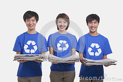 Three smiling young people standing in a row carrying newspapers and wearing recycling symbol t-shirts, studio shot